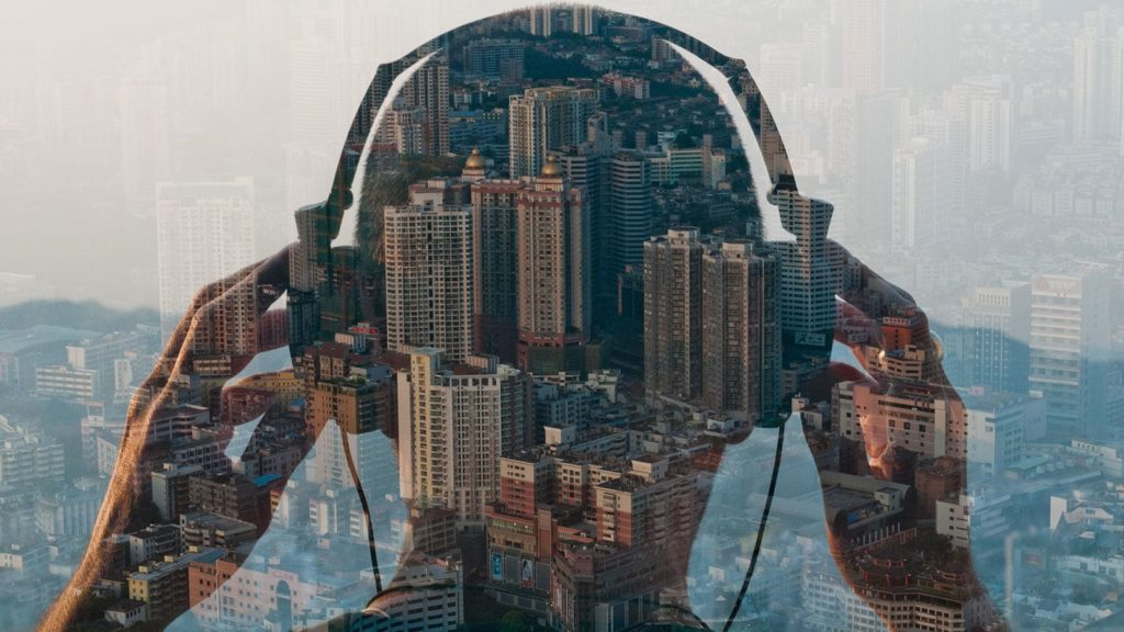 Guy using Headphones, looking at the city from a skyscraper